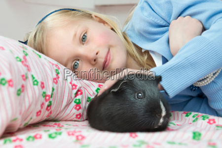 portrait of young girl stroking pet