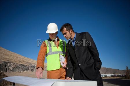 2 men examining blueprints outside