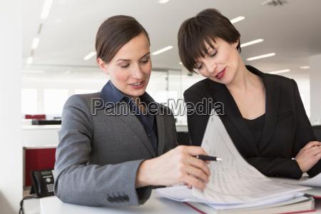 businesswomen working at desk together