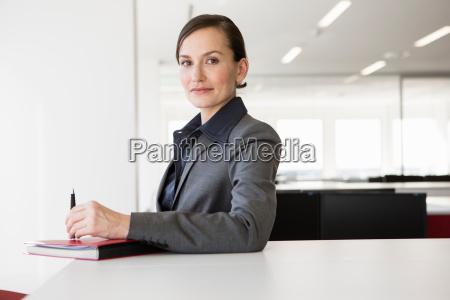 businesswoman, at, desk, holding, pen - 19543764
