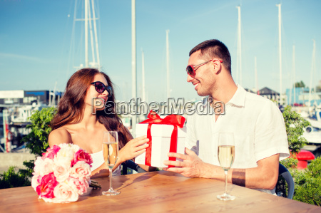 smiling couple with gift box cafe