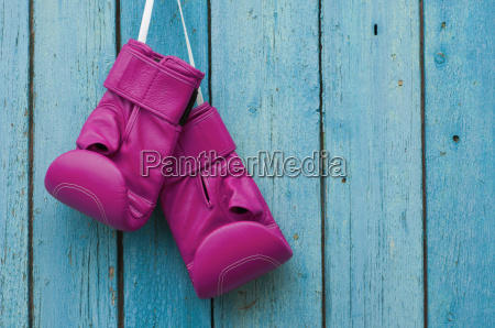 rosa boxhandschuhe auf blau geknackt holzuntergrund