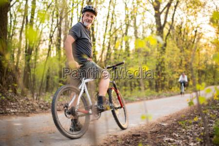 aelterer mann auf seinem mountainbike im