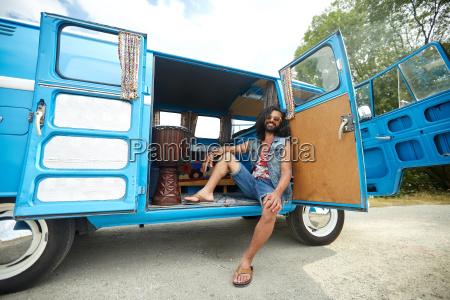 smiling young hippie man in minivan