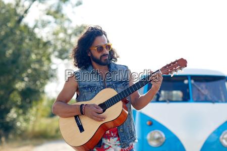 hippie man playing guitar over minivan