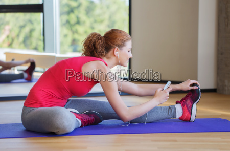 smiling woman stretching on mat in