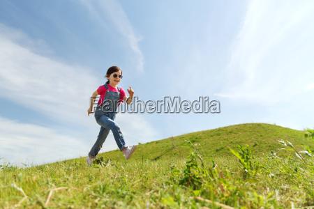 happy little girl running on green