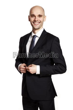 man in black suit smiling to