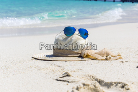 hat with sunglasses on the beach