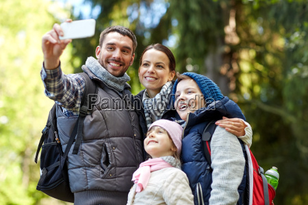 family taking selfie with smartphone in