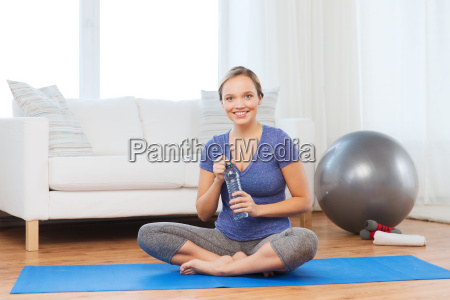 happy woman with water bottle exercising