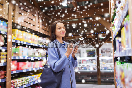 happy woman with notepad in grocery