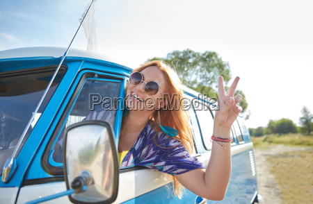 smiling young hippie woman driving minivan