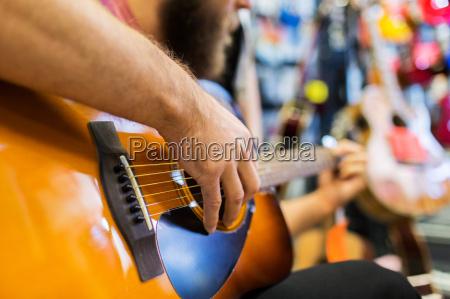 close up of man playing guitar
