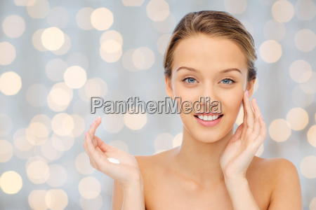 happy young woman applying cream to