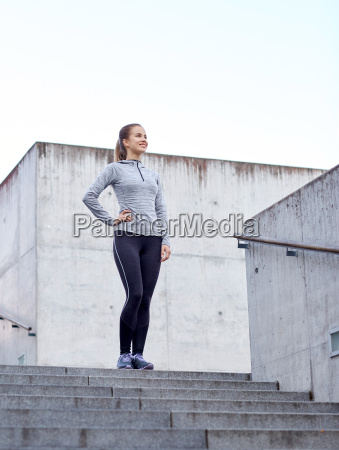 smiling sportive woman on stairs at