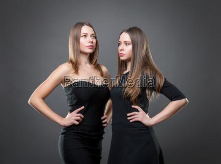 portrait von zwillingen in schwarzen kleidern