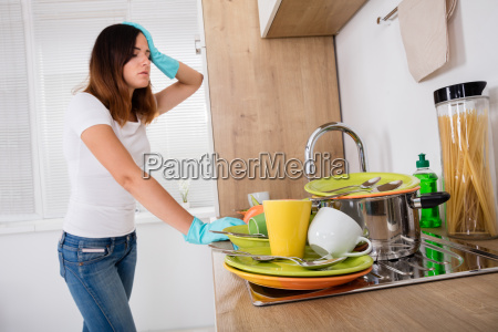 exhausted woman standing in kitchen