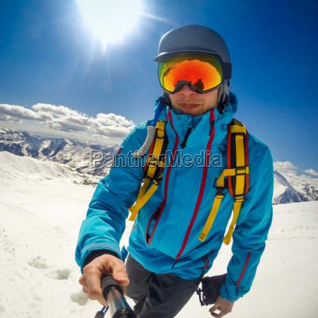 snowboarder taking selfie while climbing mountain