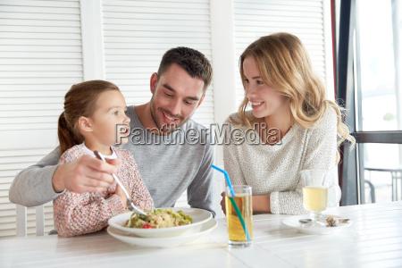 happy family having dinner at restaurant