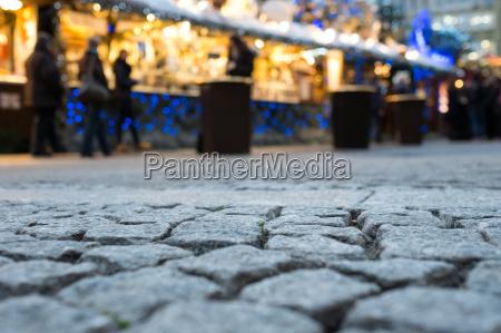 kopfsteinpflaster am weihnachtsmarkt mit unscharfen lichtern