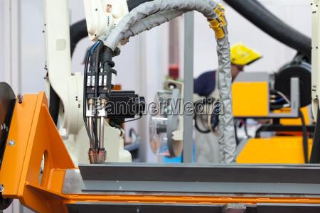 industrieller schweissroboter arm im fokus verschwommener