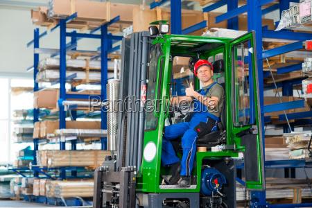worker in factory in lift truck