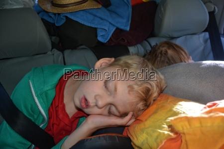 zwei kinder schlafen im vollbepackten auto