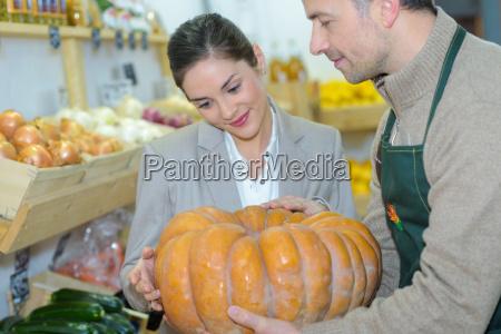 grocer kuerbis zeigt kunden