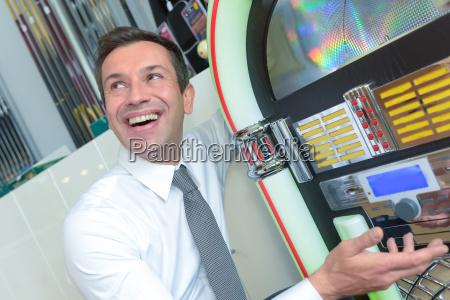 junger mann spielt einen spielautomaten