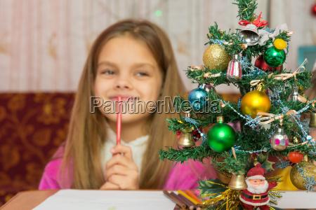 maedchen denkt froehlich ueber ein geschenk