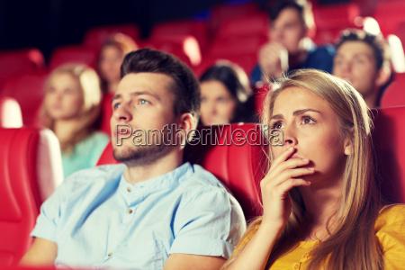 glueckliche freunde beobachten horrorfilm im theater