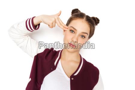 bored teenage girl making finger gun
