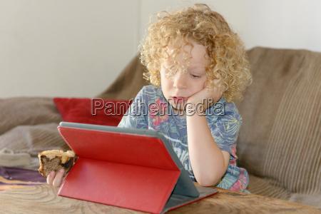 little blond boy using tablet computer