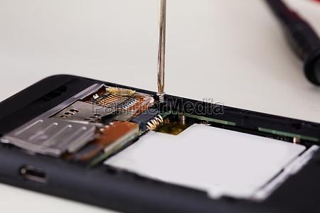 broken mobile phone with screwdriver