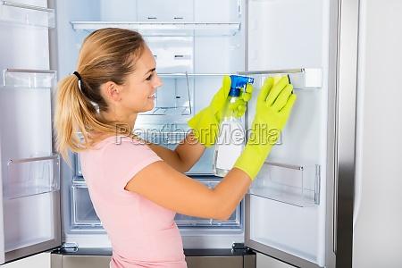 woman cleaning the empty refrigerator door
