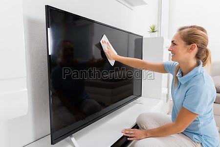 frau wischen fernsehen des wohnzimmers