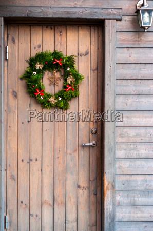 weihnachtsdekorationen auf einer hoelzernen tuer