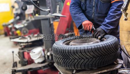 professionelle automechaniker reifen auf dem rad