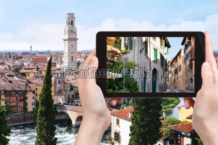 tourist photographs street in verona city