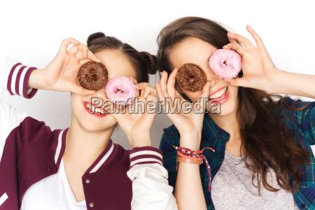 glueckliche huebsche teenager girls mit donuts