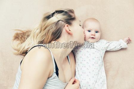 mutter kuessen maedchen ihr kind baby