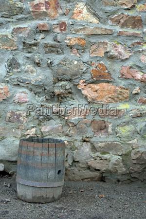 fass aus holz an einer steinwand