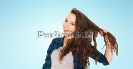 happy teenage girl holding strand of