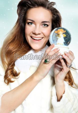 freudige weihnachtsfrau in einem weissen pelzmantel