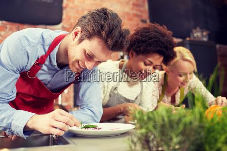 glueckliche freunde kochen und dekorieren gerichte