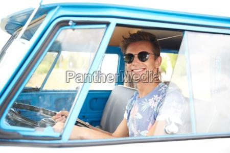 smiling young hippie man driving minivan