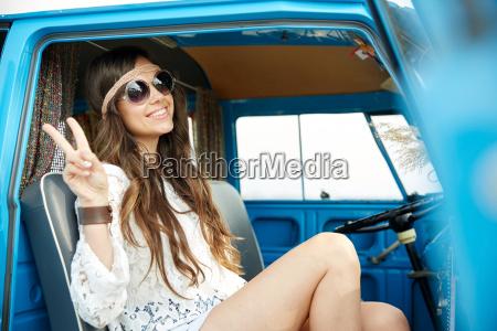 happy hippie woman showing peace in