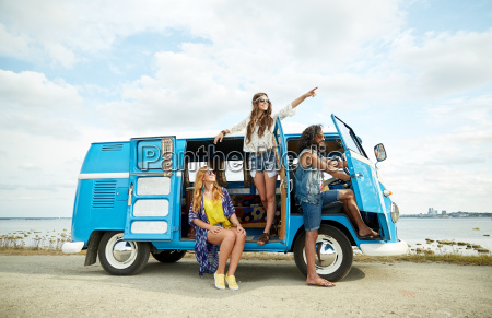 smiling young hippie friends over minivan