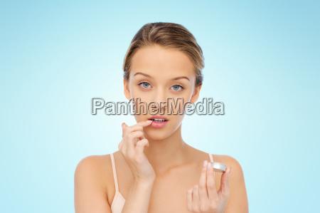 junge frau anwendung lippenbalsam auf ihre